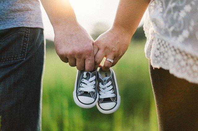 赤ちゃんの靴を握っている夫婦