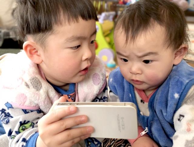 iPhoneを見ている二人の男の子